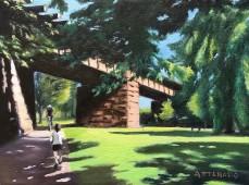 Biker and jogger on trail beneath railroad bridge in sunlit park